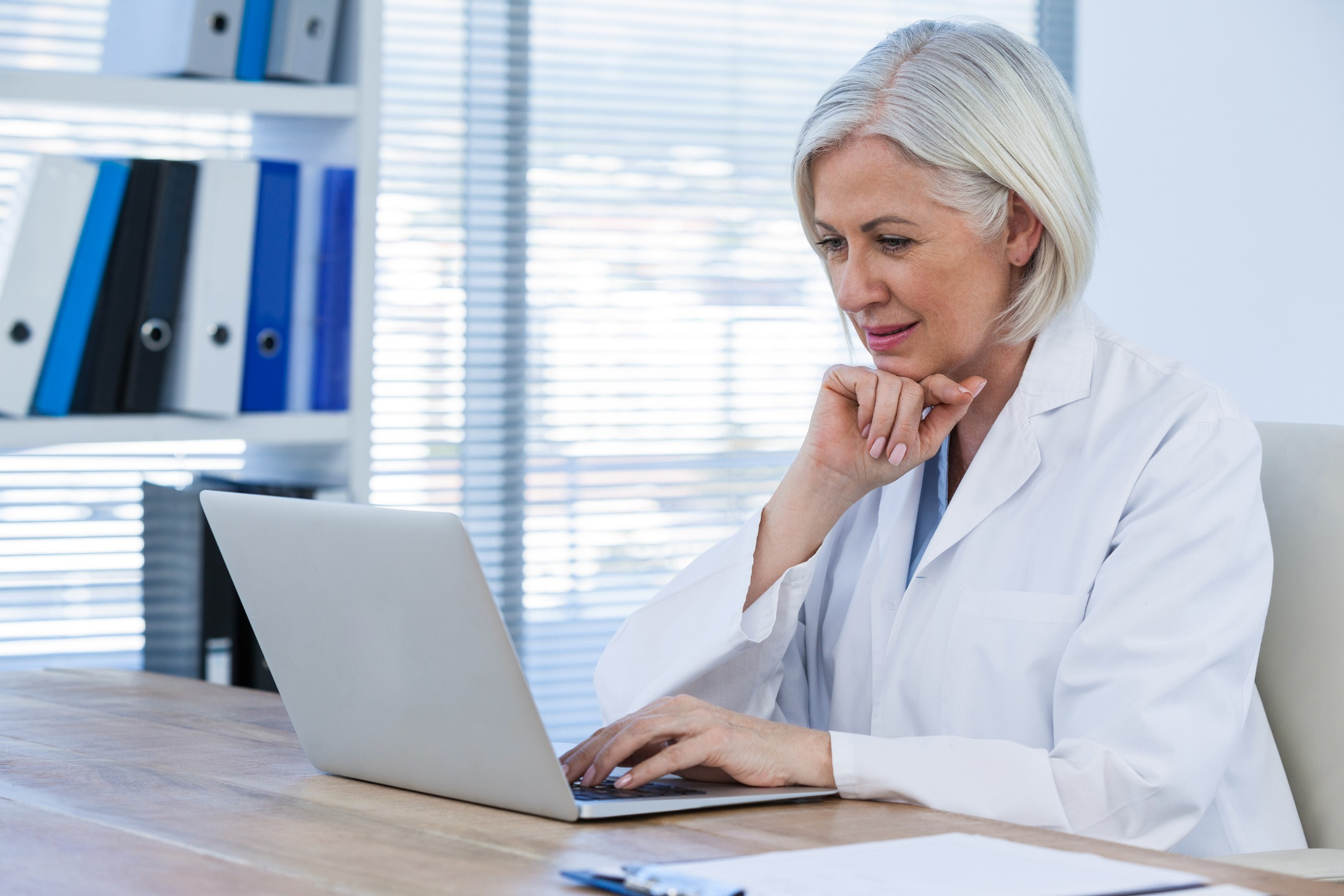 Thoughtful female doctor working on her laptop in clinic