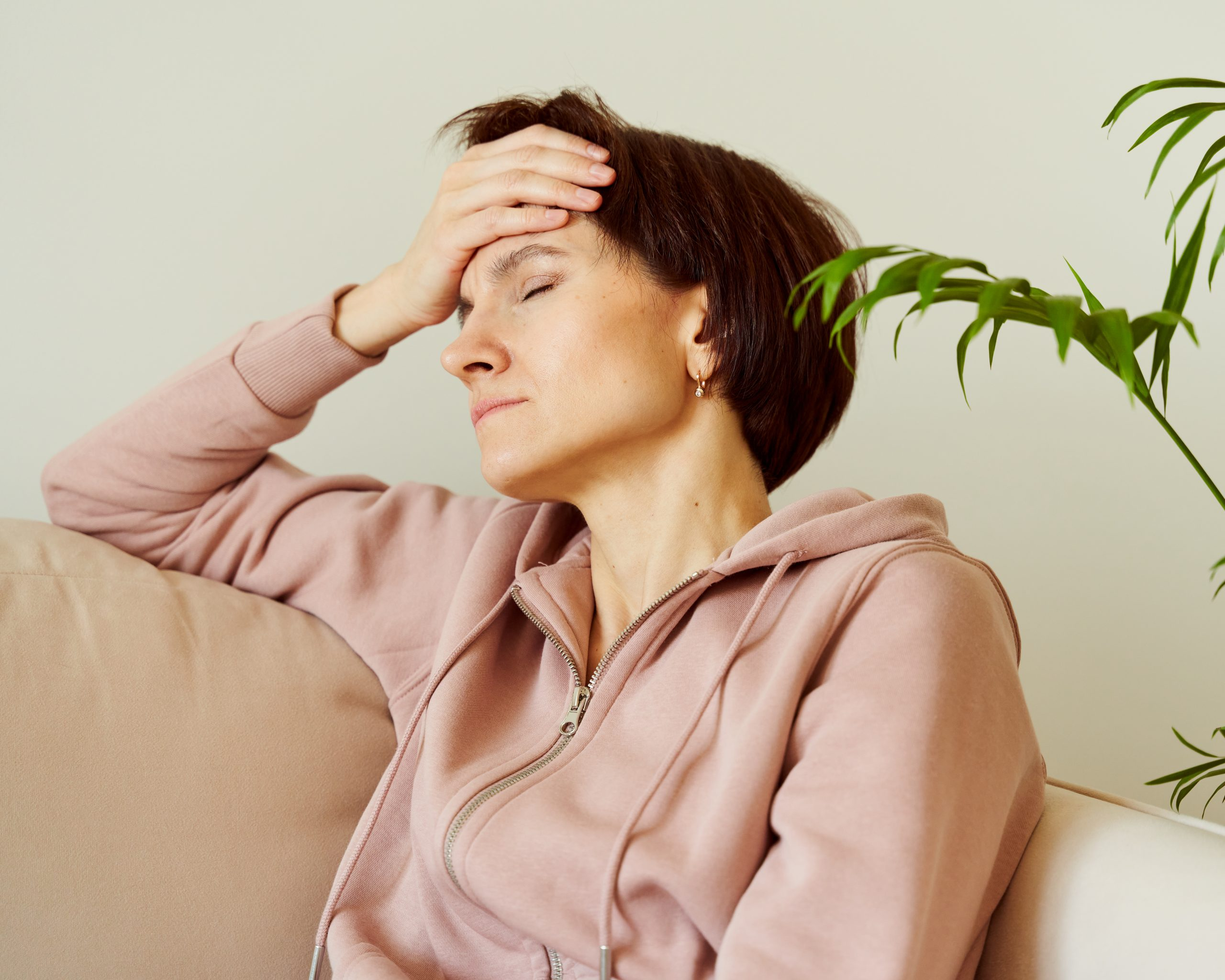 Woman putting hand on head due to headache after waking up, filling deep sadness. Migraine. Mental health of mature female, generation X. Tired lady sitting in home with closed eyes