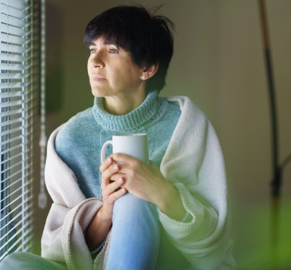 Mid adult woman drinking coffee and looking out of the window in winter day. Female in her 50s
